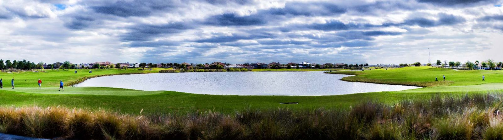 Panoramic view of playing on multiple hole surrounding one of Duran Golf club's largest ponds