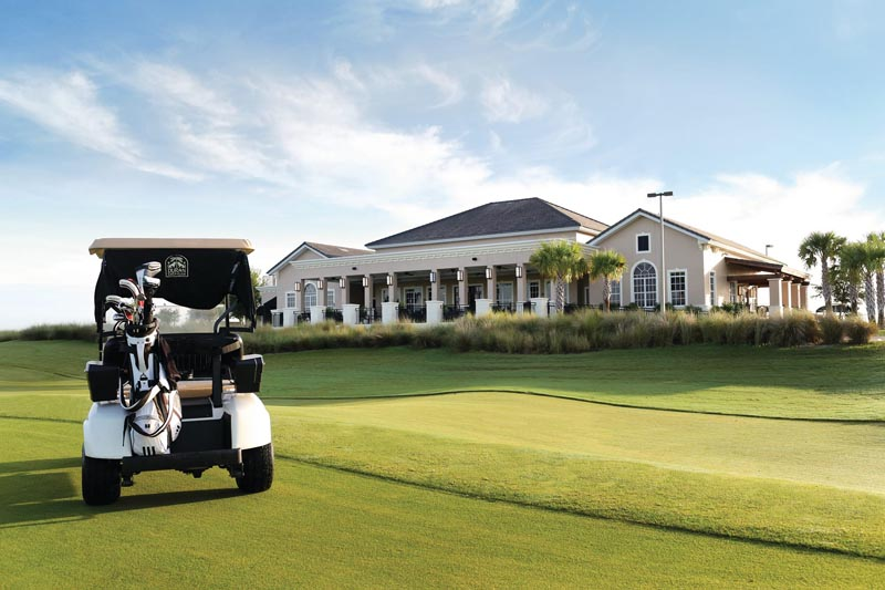A golf cart sits in front of the clubhouse at Duran Golf Club