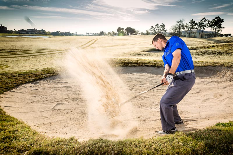 A man hits a golf ball out of a sand trap at Duran Golf Club